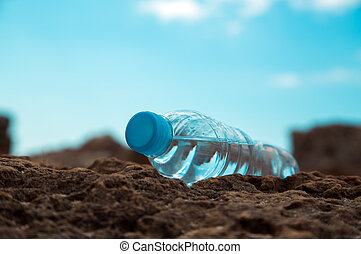 pet bottle with water on the sea sand.