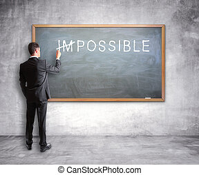 impossible - businessman drawing impossible text on a chalk...