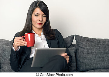 Attractive woman reading on a tablet pc
