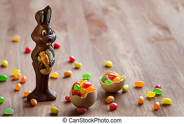 Chocolate Easter Bunny with sweet candy on the wooden table