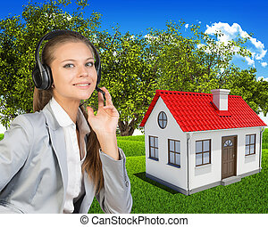 Businesswoman in headset, small house and green landscape as backdrop