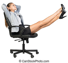 Businesswoman on office chair with her feet up -...
