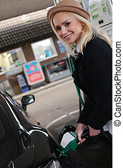 Smiling woman filling the car with fuel