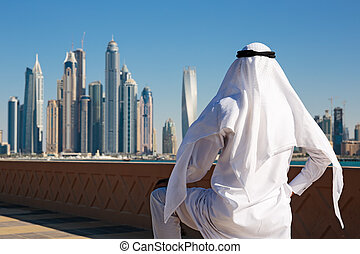 Modern buildings in Dubai Marina, UAE. Man in Arab dress...