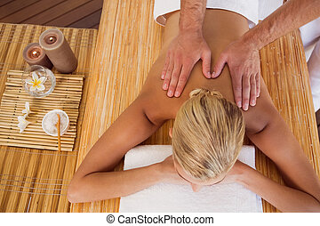 Woman receiving back massage at spa center - High angle view...