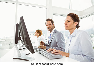 People using computers in office - Side view of business...