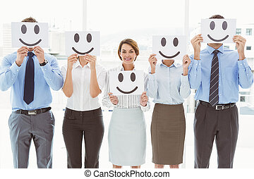 Business people holding happy smileys in front of their...