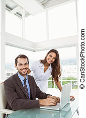 Business people using laptop - Portrait of two young...
