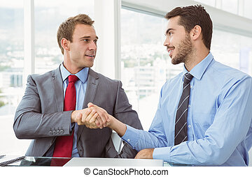 Executives shaking hands in board room meeting at office