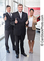 Smiling business team standing while giving thumbs up at new...