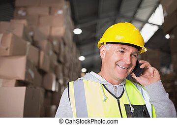 Worker using mobile phone in warehouse - Worker in hard hat...