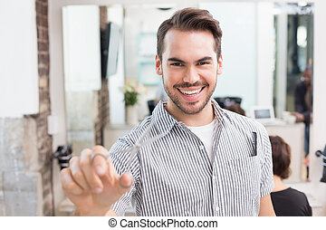 Handsome hair stylist holding scissors at the hair salon