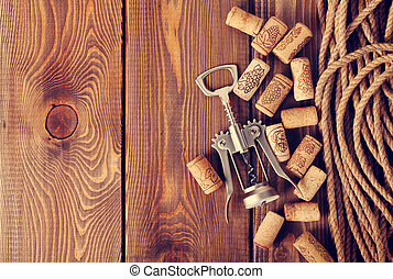 Wine corks and corkscrew over rustic wooden table background...
