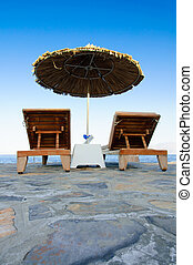 Chairs and umbrella on a beach - Two chairs and umbrella on...
