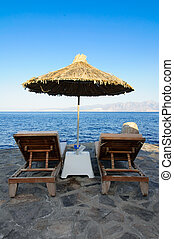 Chairs and umbrella on a beach - Two chairs and umbrella...