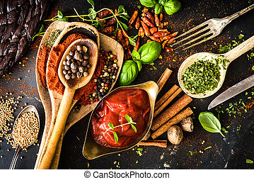 tomato sauce with spices and textured black kitchen table
