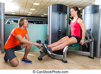 Calf extension woman at gym exercise machine workout and...
