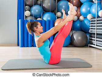 Pilates Open Leg Rocker exercise on mat woman with balls...