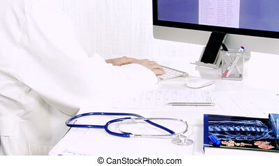 Doctor writing text on pc