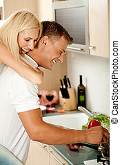 Piggyback fun - Female enjoying piggy ride in kitchen as man...