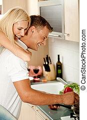 Piggyback fun - Female enjoying piggy ride in kitchen as man...