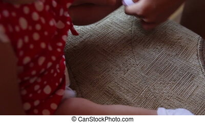 Mom puts sock to her baby - Mom puts white sock to her baby