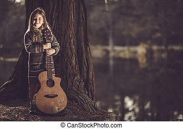 Girl With Guitar in the Park. Little Caucasian Girl with...