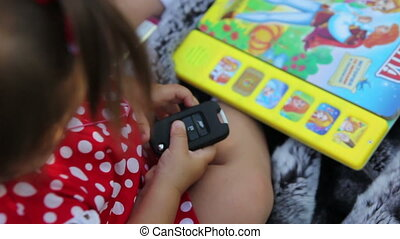 girl playing with the car keys - girl sitting at grass and...