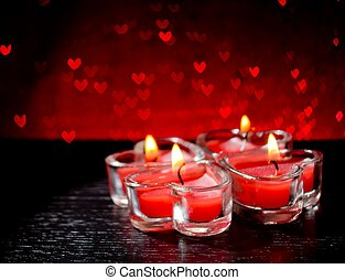 red burning heart shaped candles on red hearts bokeh...