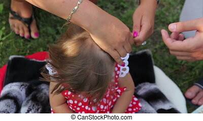 rite of cutting hair of child - woman cut girl hair with...