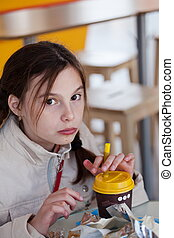 Girl eating a hot dog in a cafe.
