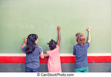 Multi ethnic schoolmates writing math at chalkboard