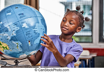 African primary school girl studying world globe in the...