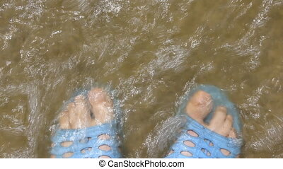 Human legs in blue slippers and Sandy river bank with waves...