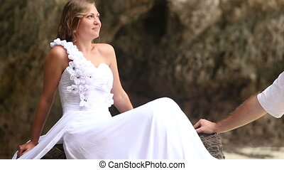 bride speaks and looks at groom on rock at  beach