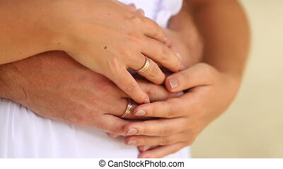 groom and bride arms with wedding rings