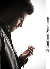 casual business man looking down at his fingers. - Side view...