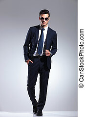 Full length picture of a elegant business man posing on grey...