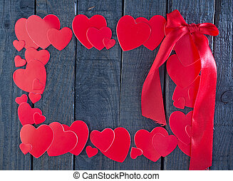 red hearts from paper on the wooden board