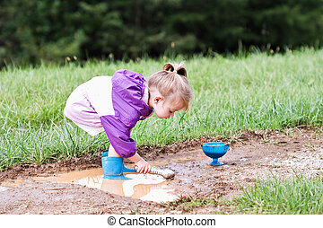 Child playing in the mud - Cute little girl playing in the...