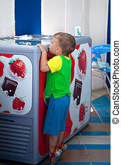 Thirst of ice-cream - The little boy looks in a refrigerator...
