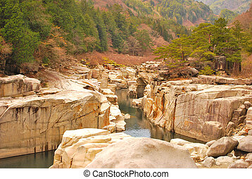 Ravine surrounded with huge rocks - A majestic ravine formed...