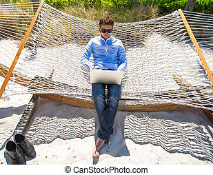 Young man working with laptop in hammock during beach...