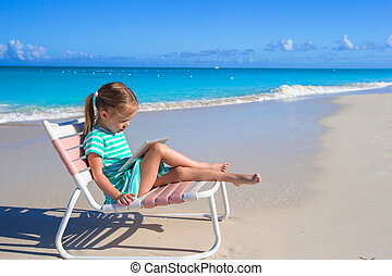 Little adorable girl with laptop on beach during summer...
