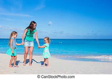 Young happy mother and little girl having fun during beach...