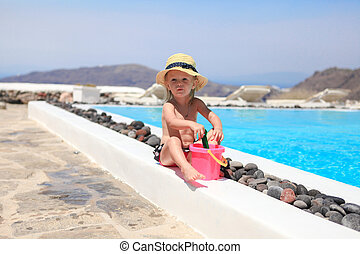 Adorable little girl near pool during greek vacation in...