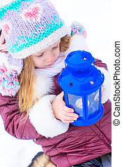 Adorable little girl holding Christmas lantern outdoors on...