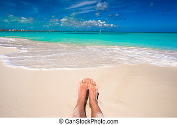 Close up of female feet on white sandy beach - Close up of...