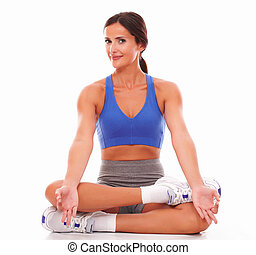 Sporty young woman doing relaxation exercise against white...
