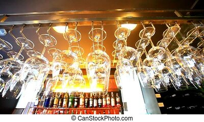 Empty glasses hanging at the bar and Bar with bottles...
